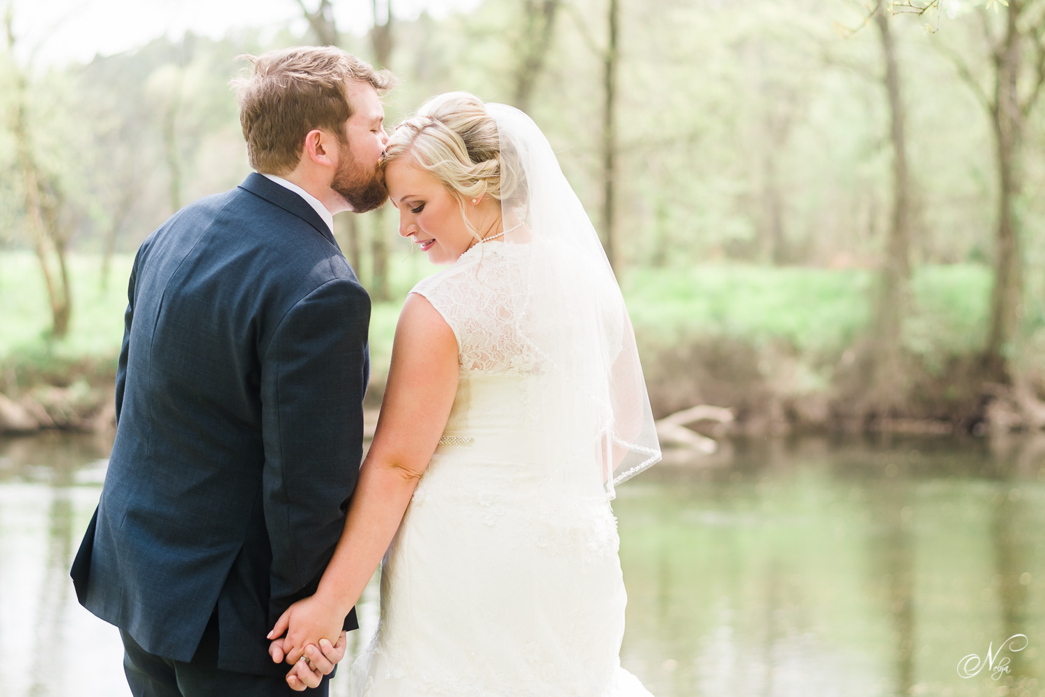 groom and bride in early april on the edge of the river in Tennessee.
