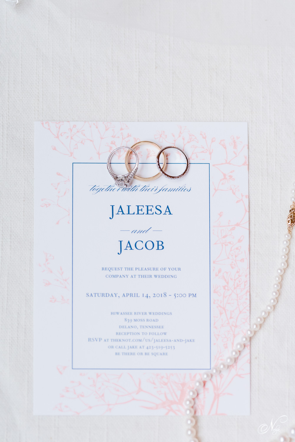 wedding invitation in blush and navy and wedding rings on white styling board.
