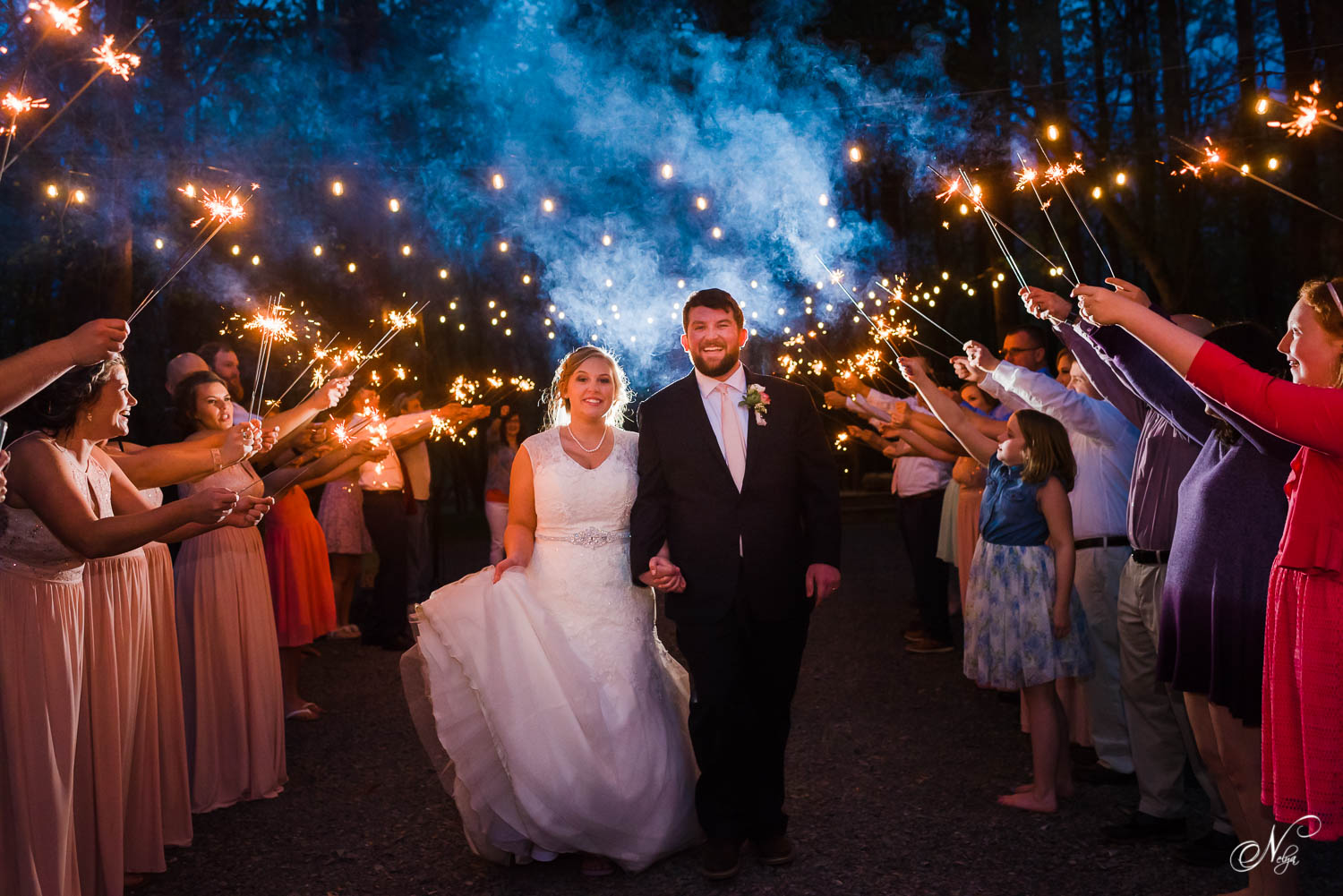 bride and groom walking under sparklers held by guests hoping not to get burnt
