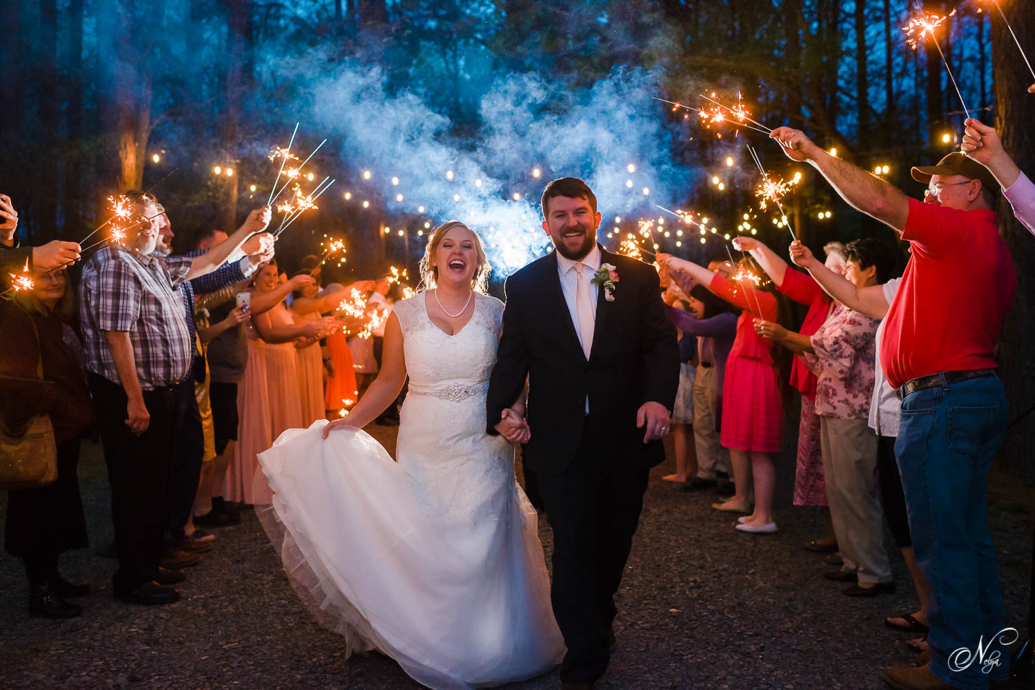 bride and groom running and laughing under sparkler exit in east TN at Hiwassee River Weddings in Delano TN