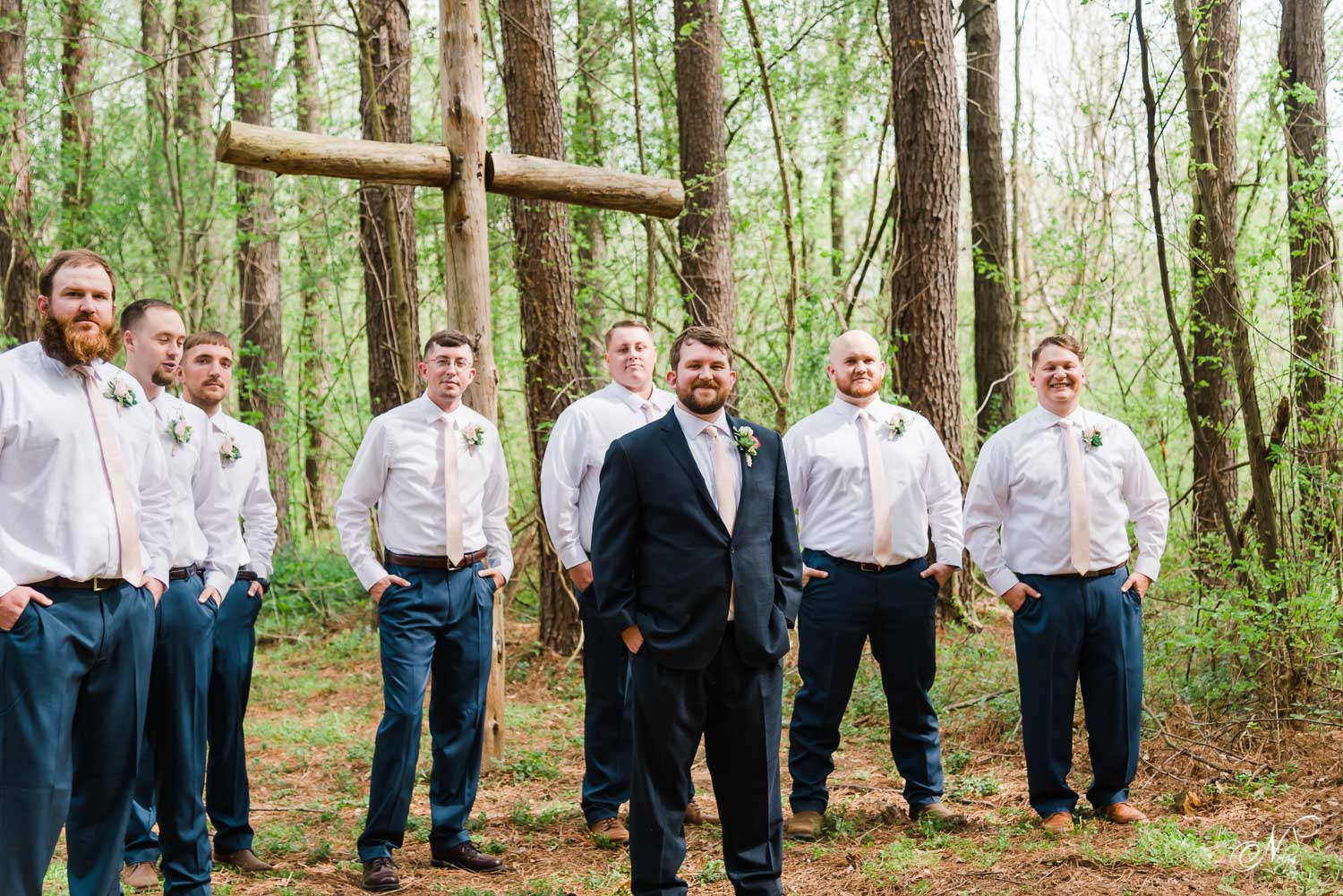 groom and broomsmen walking under the tall pines at south east Tennessee wedding venue