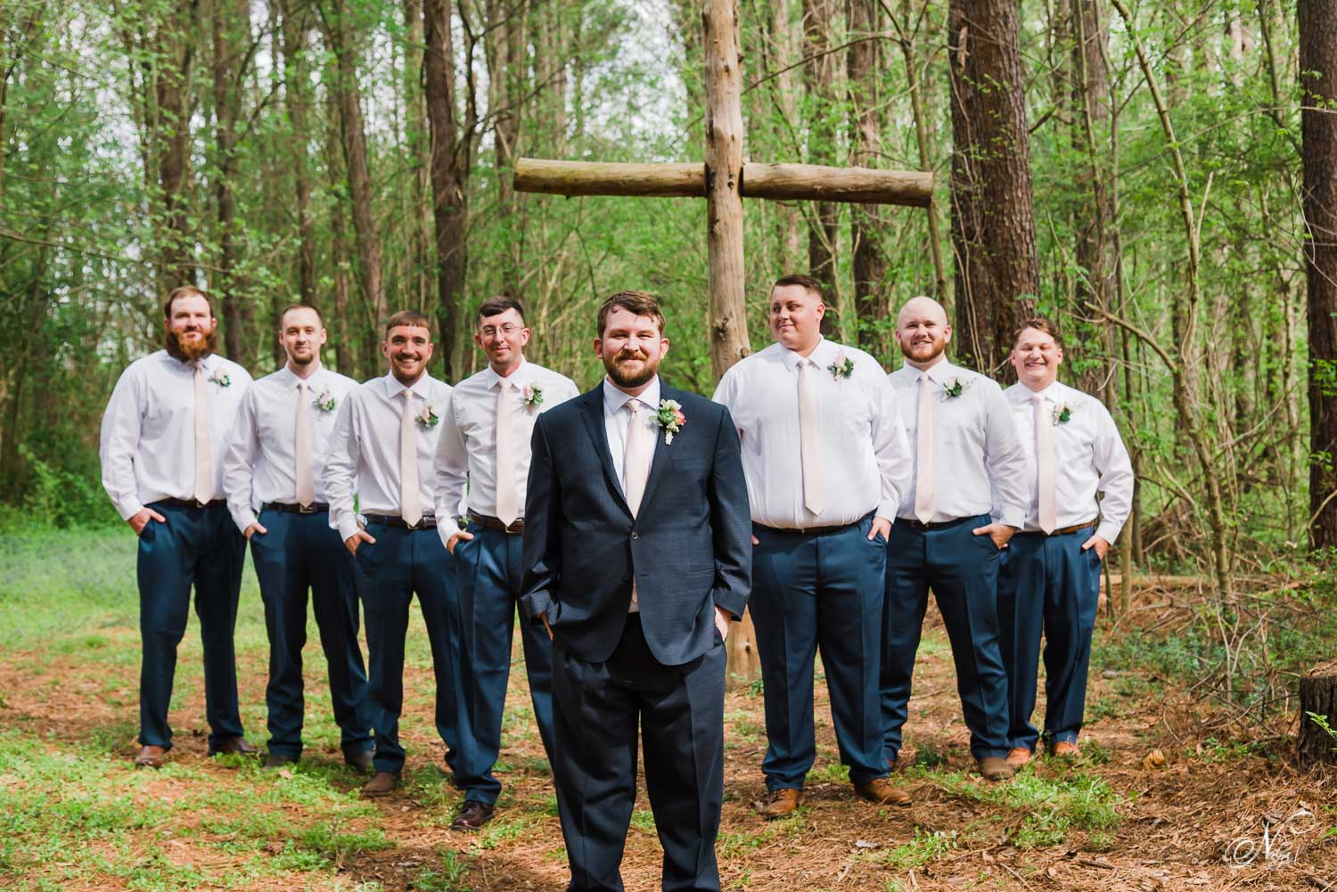 groom and groomsmen in front of large wooden cross at Hiwassee river weddings