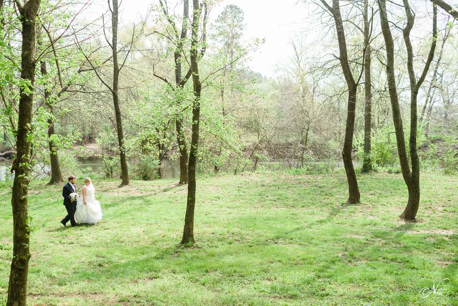 little tiny bride and groom walking through big bright green early spring trees near Chattanooga.