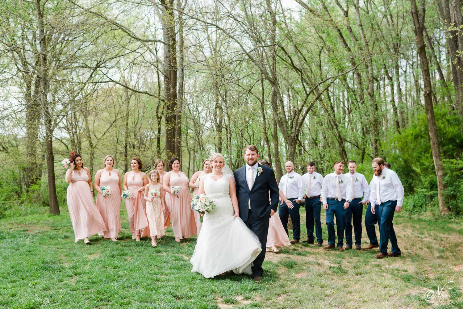 blush and navy wedding party in background with bride and groom in front