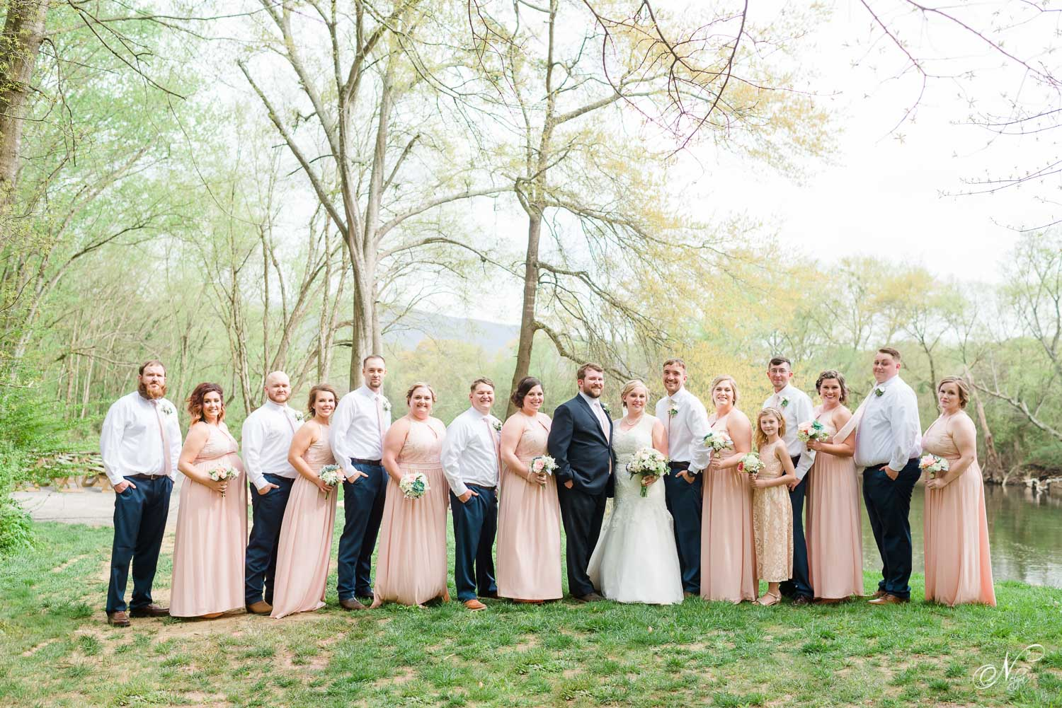 blush and navy wedding party in front of the riverside ceremony area at Hiwassee River weddings venue