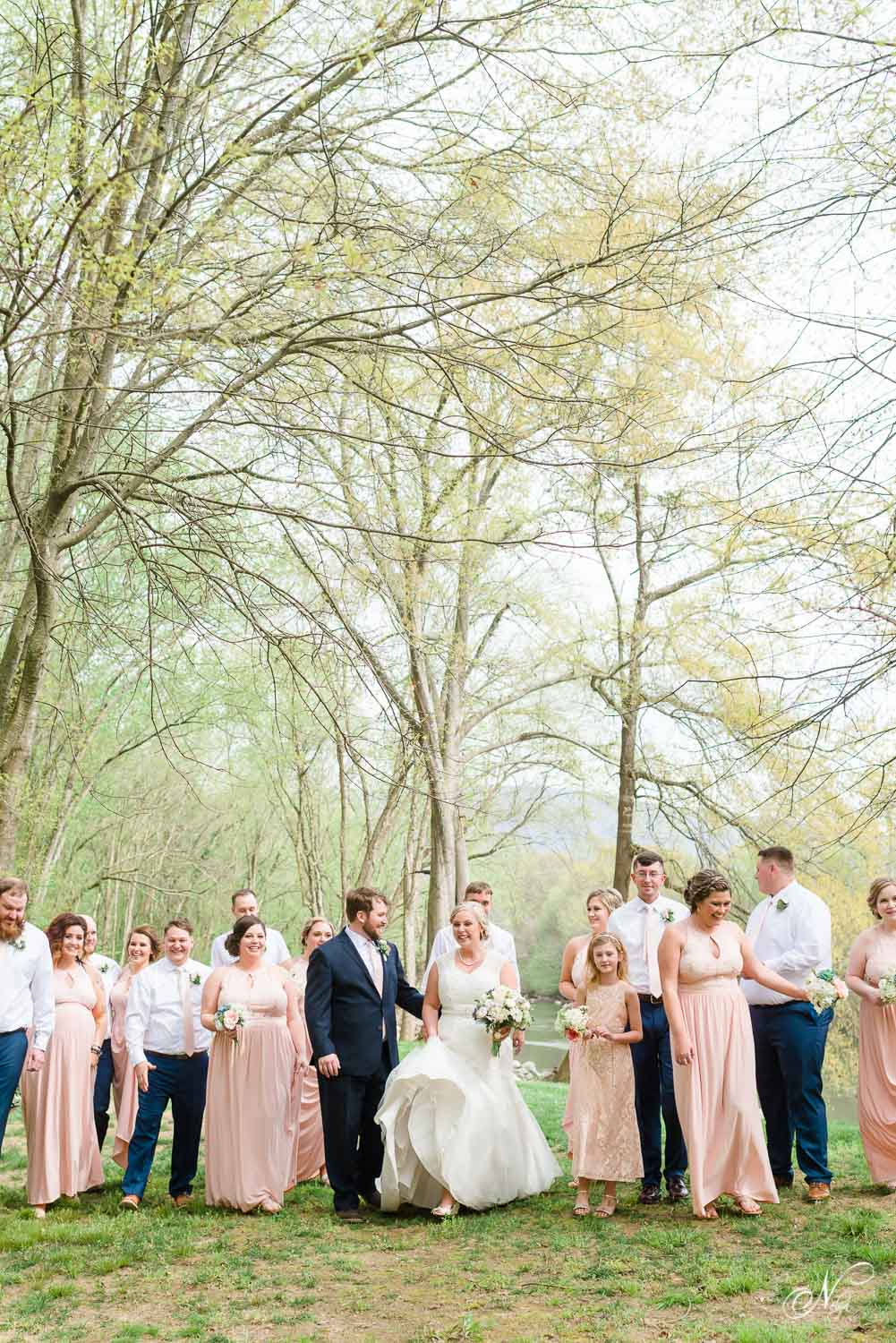 bride in wedding dress with short train, groom and groomsmen in navy blue and white at april wedding on the Hiwassee river in Delano TN