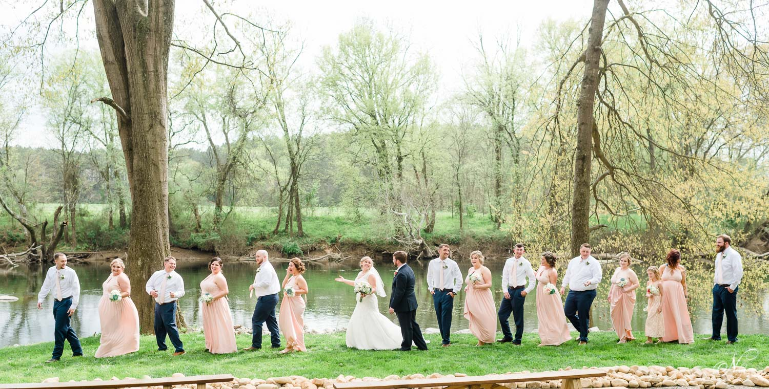 bridal party walking along river edge single file wearing blush and navy