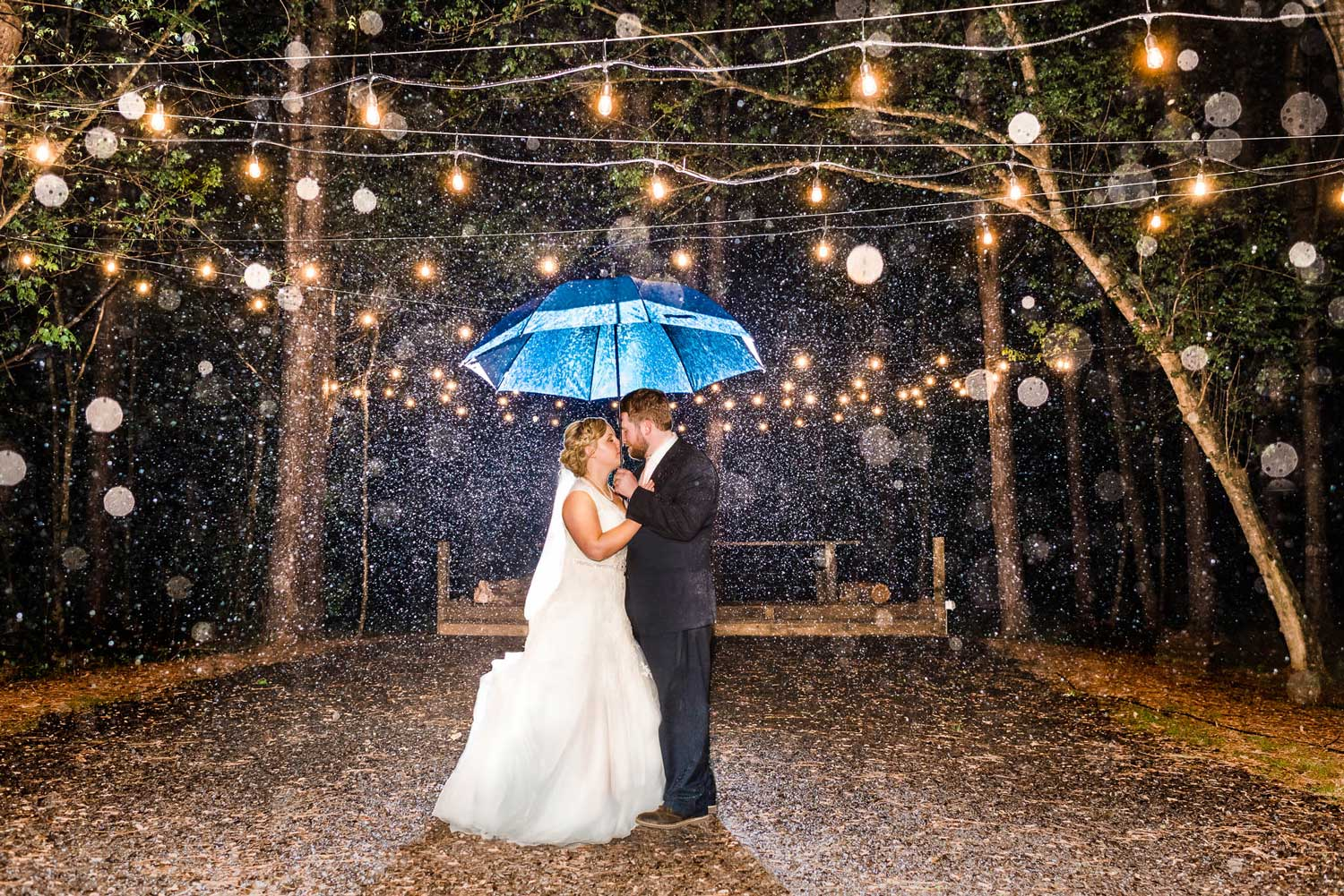 wedding couple under blue umbrella in the rain at the forest ceremony site at Hiwassee River weddings.