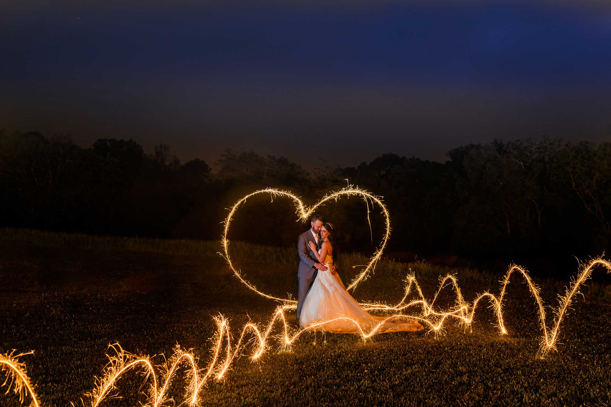 Wedding Sparklers drawn heart around couple in the dark at The Barn at Drewia Hill in Sale Creek TN