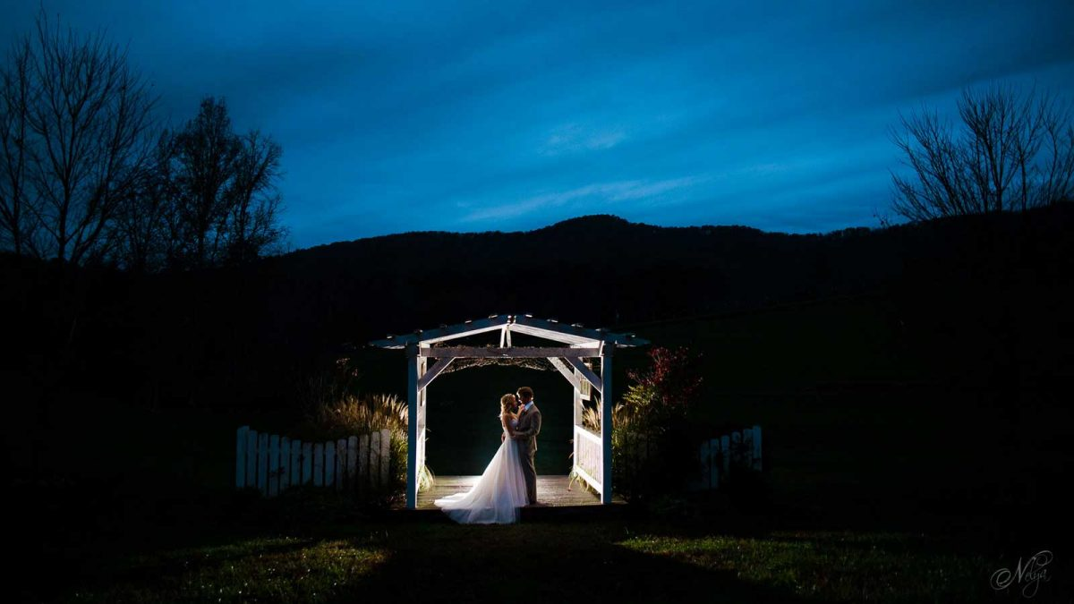 bride and groom untaer pergola at Sampsons hollow at night for wedding portraits
