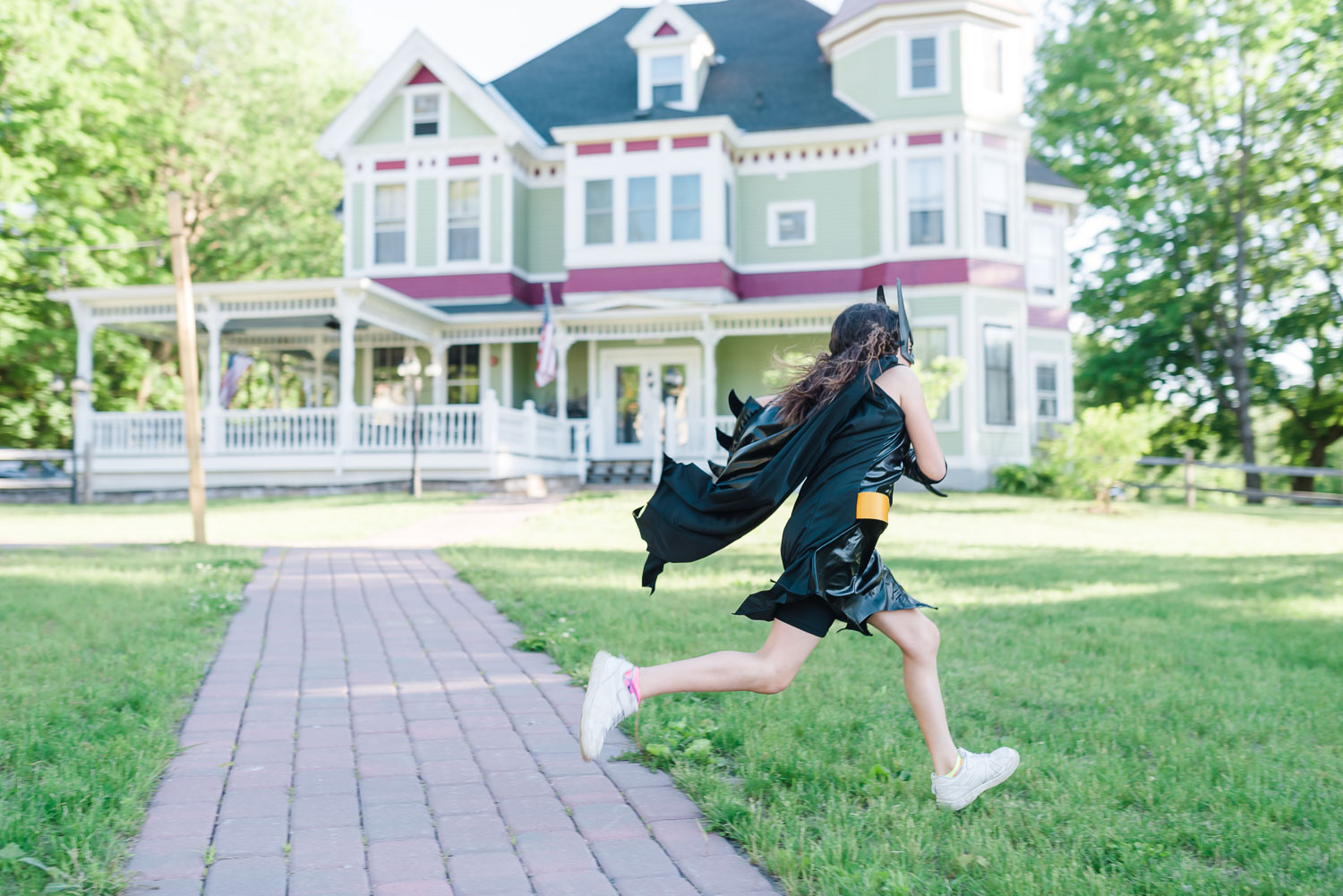 girl runningin black batman costume in front of the historic home that is now Tessie's Tavern in Bethel Vermont