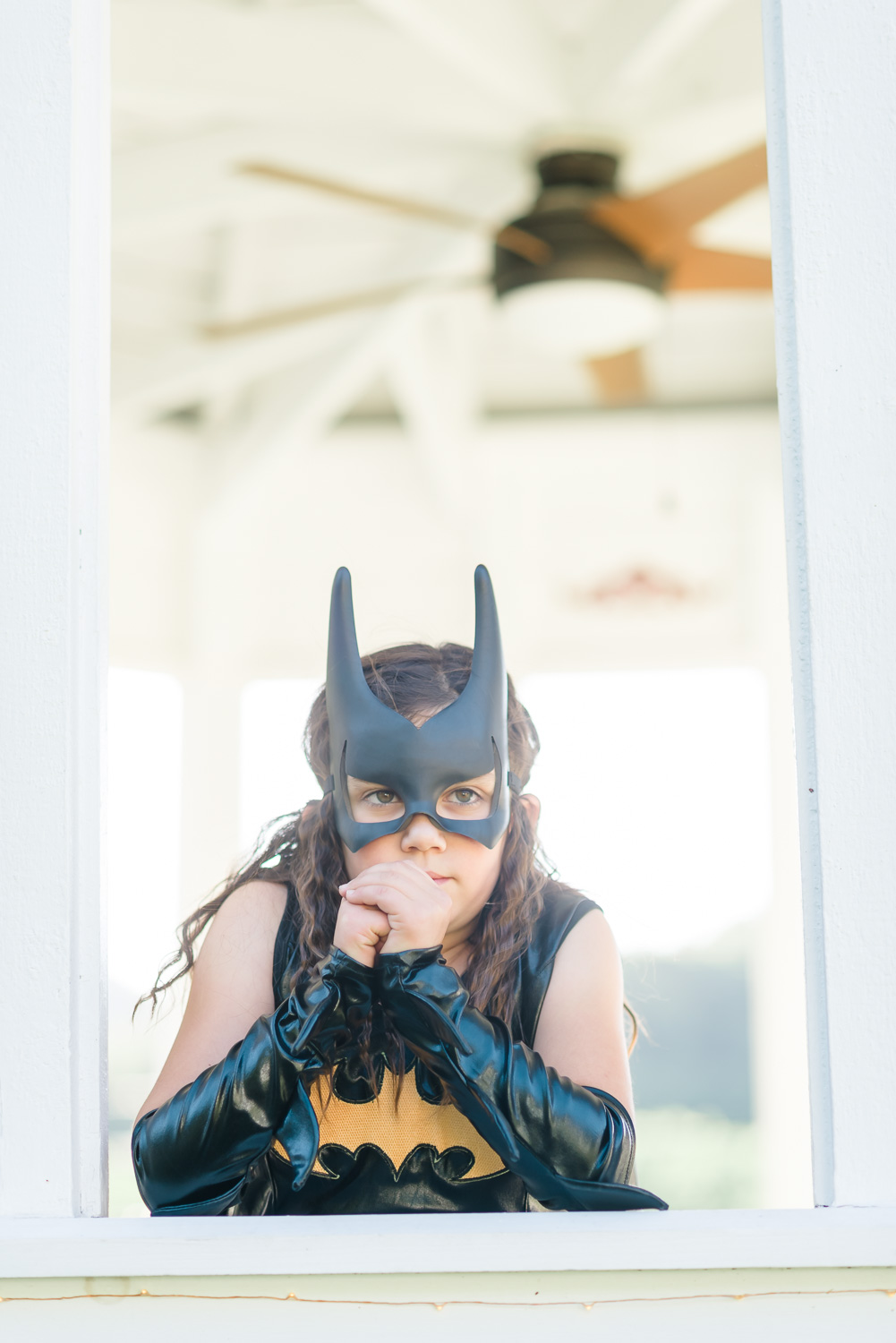 girl in pointed ear bat man mask and leather like wristlets