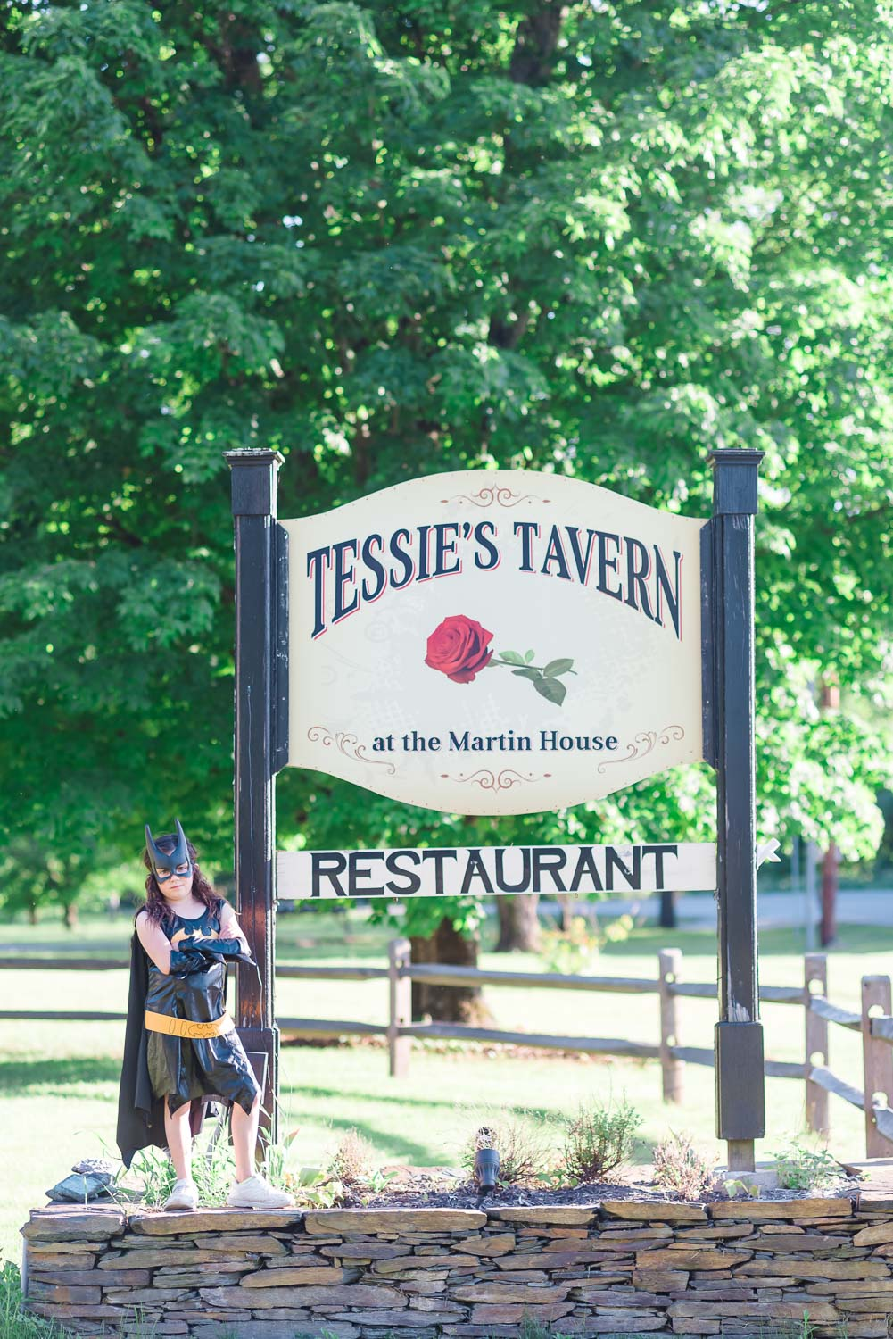 a small child in a batman costume standing next to the Tessie's Tavern sign on route 107 in Vermont