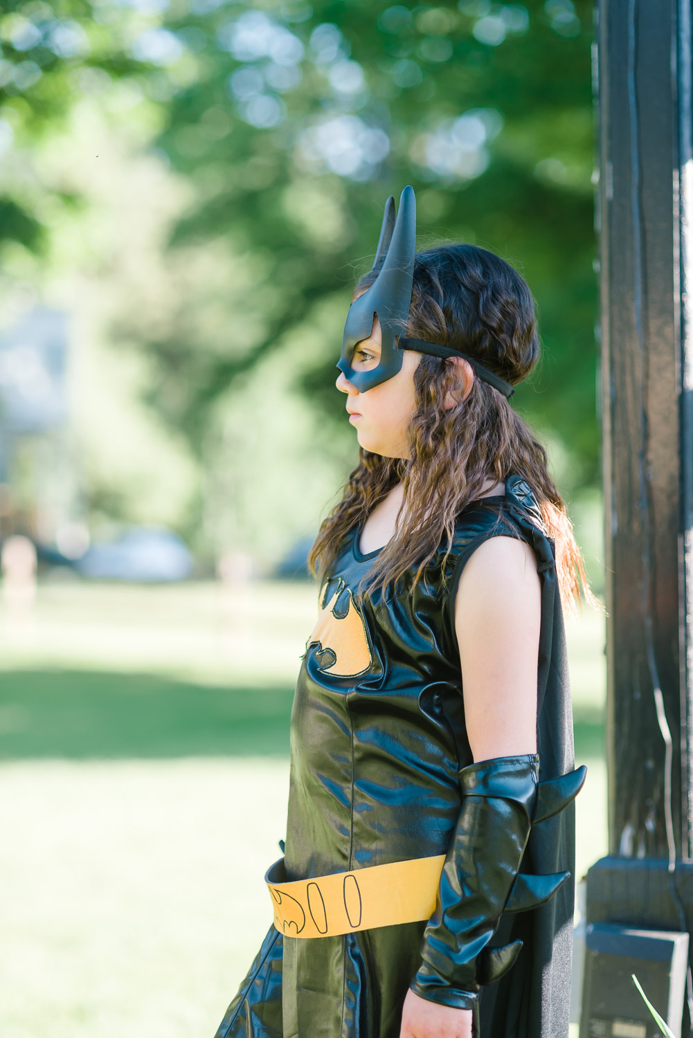 Bat girl outside under some trees looking to the side
