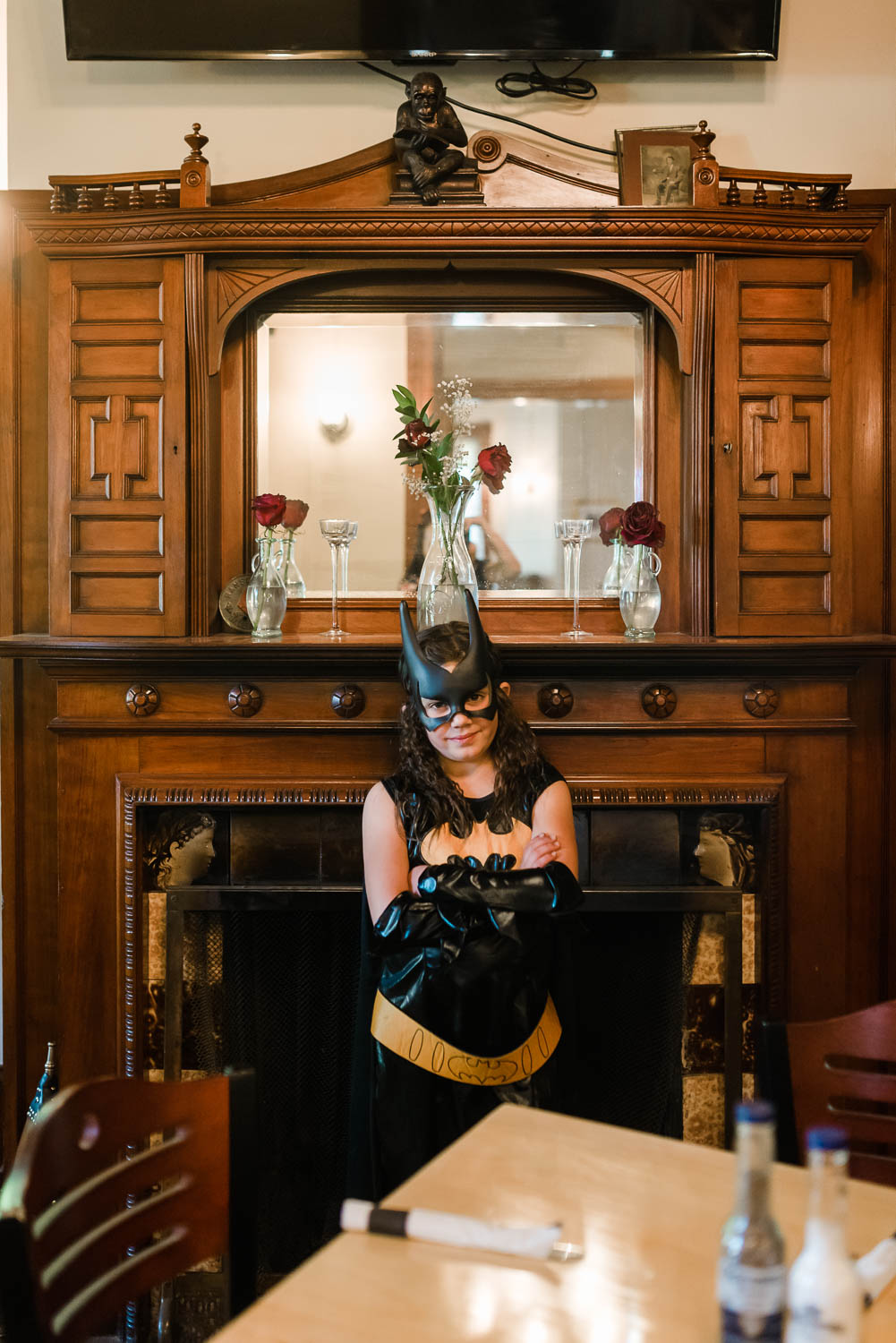 girl in batgirl costume standing in front of ornate wooden fireplace mandle at Tessie's Tavern in Bethel VT