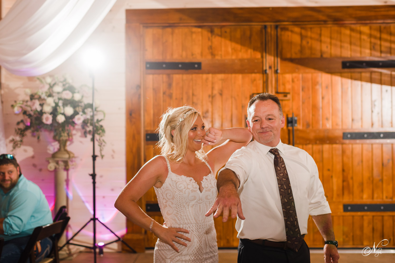 bride with her arm on her dad's shoulder as they finish their custom choreographed dance