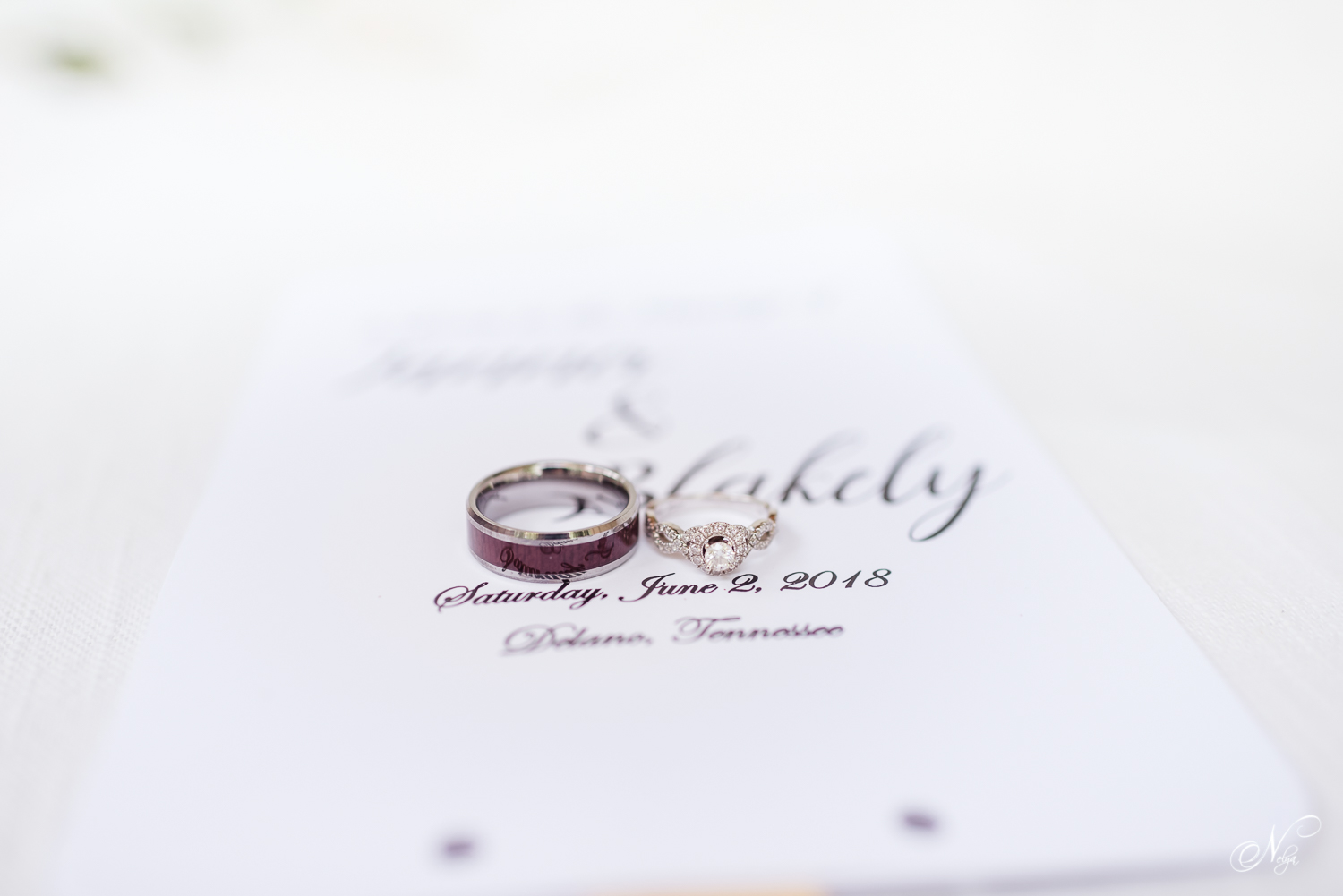 wedding rings sitting on a white invitation