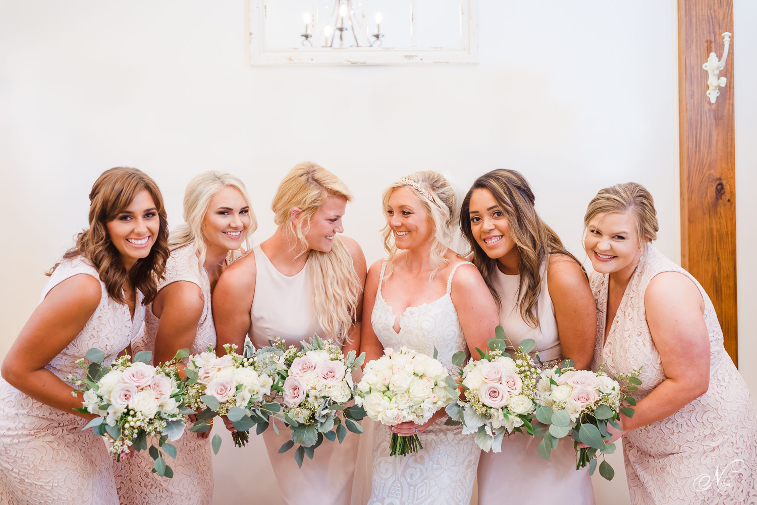 girls in long blush colored dresses and white and pale pink flowers in bridal room at Hiwassee River weddings in east Tennessee