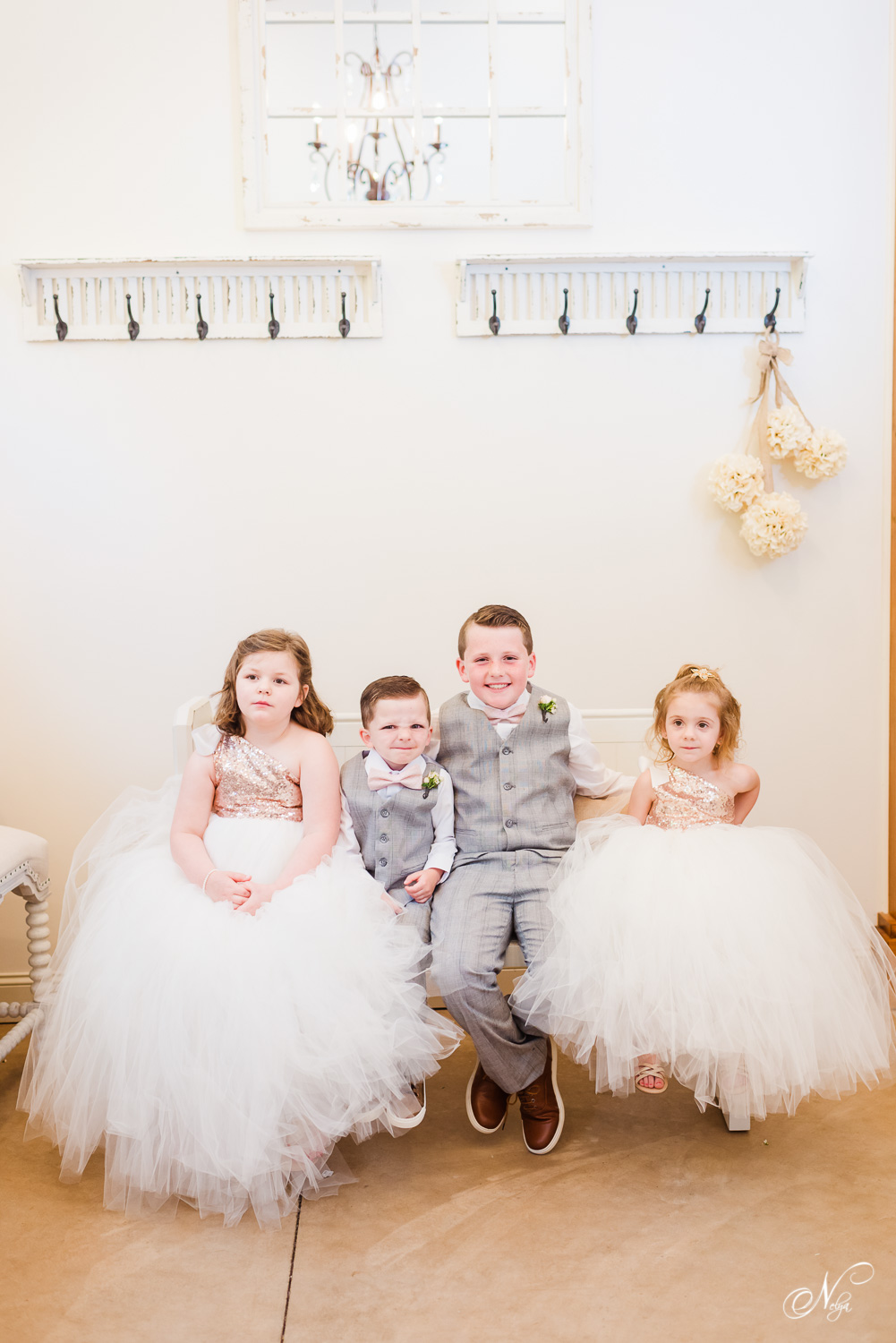 flower girls in fluffy white tulle skirts and ring bearers in gray suits