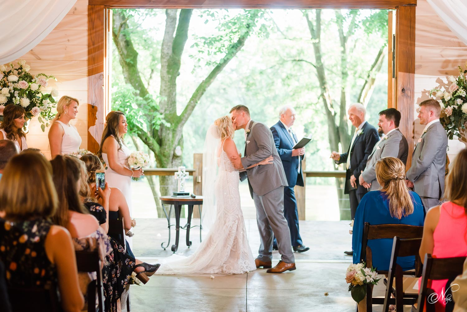 just married bride and groom kissing in the open doorway overlooking the river