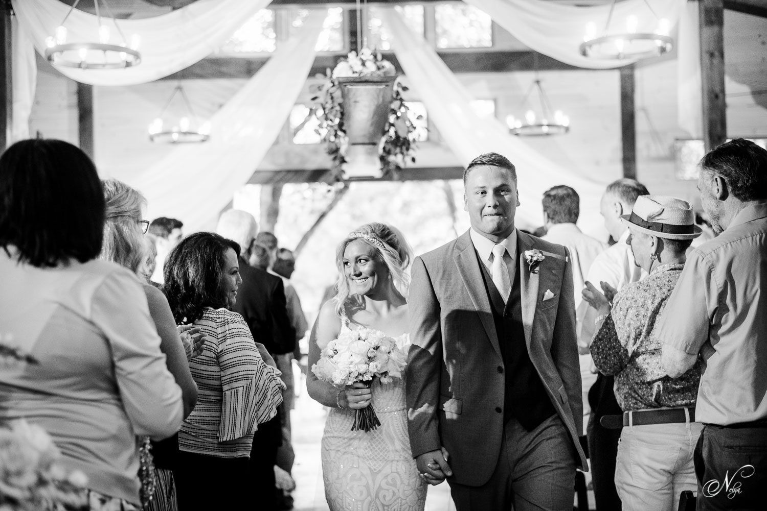 just married couple smiling as the walk back down the aisle at hiwassee river weddings first indoor wedding ceremony
