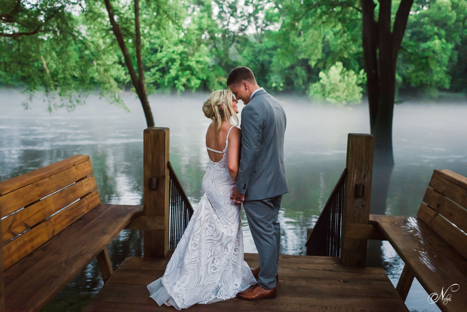 Bride and groomwatching the fog roll in across the hiwassee river at night