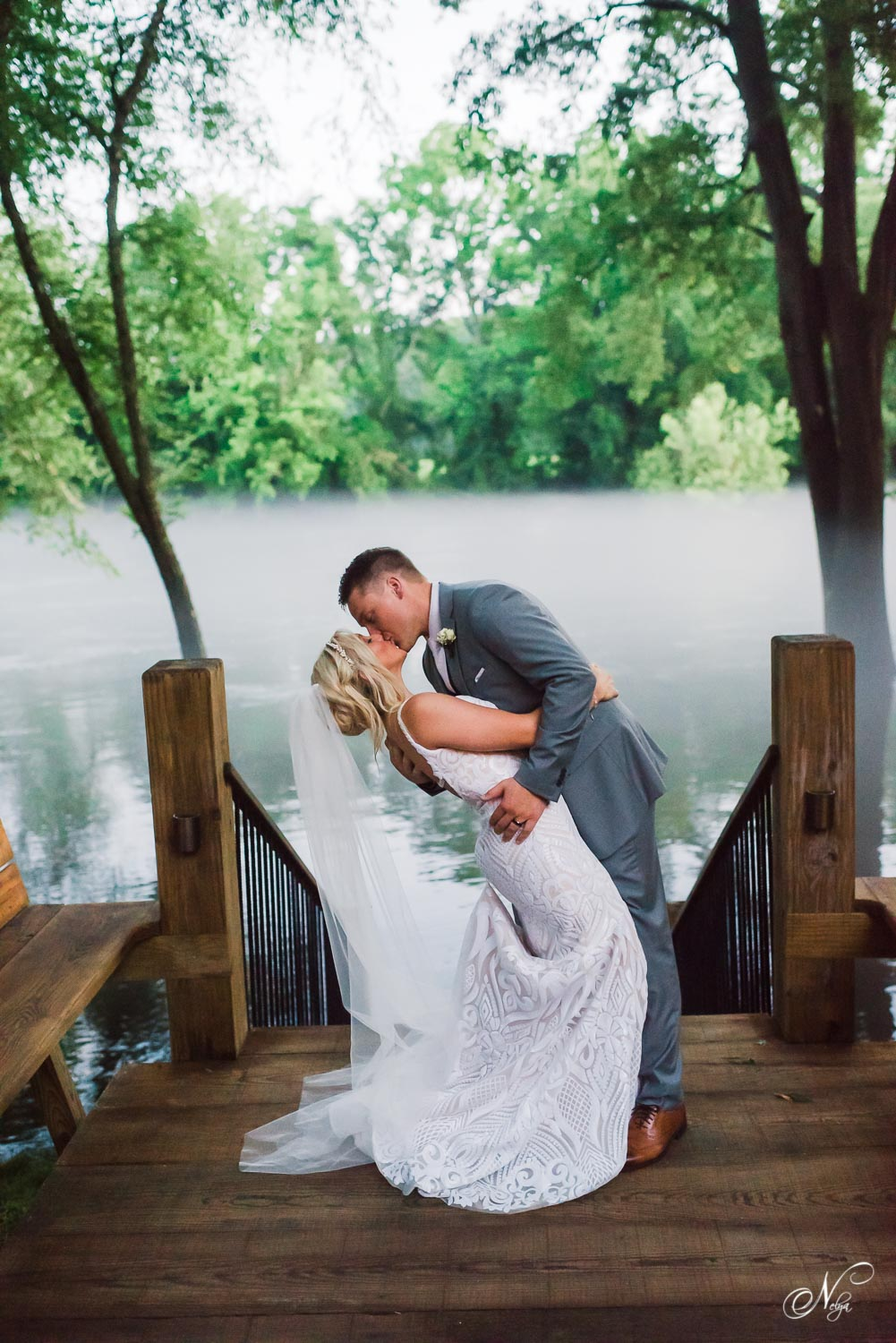 wedding couple kissing on lower stair case at Hiwassee River Weddings in the fog.
