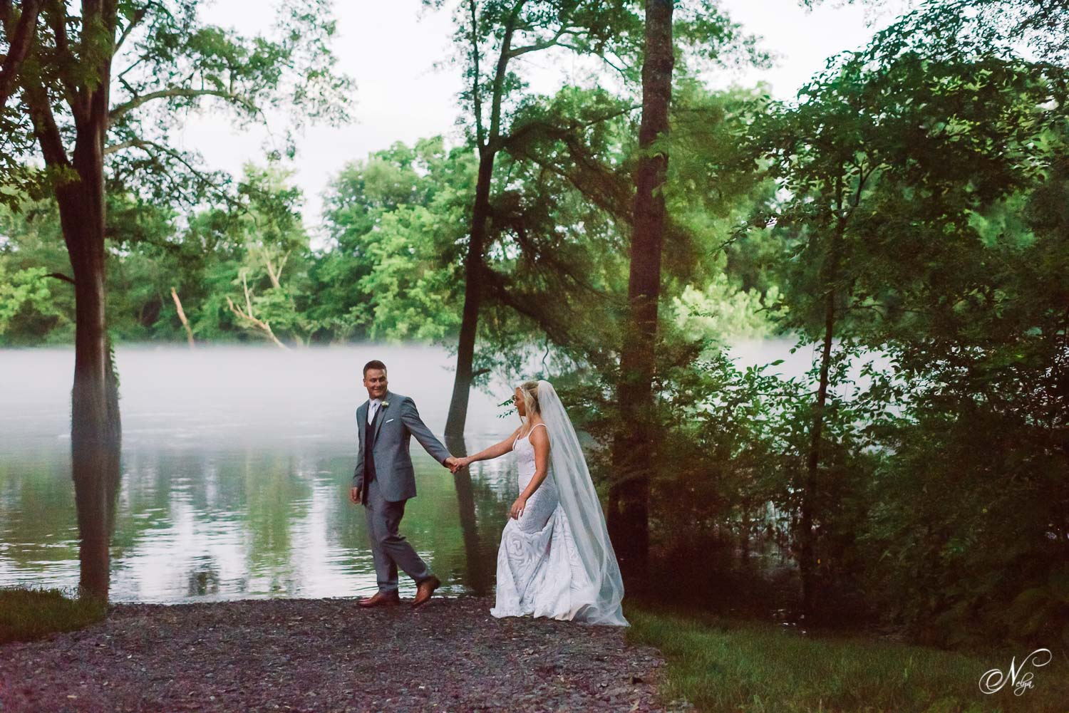 groom and bride walking in the dark along the river bank with lots of fog in the background at Hiwassee River Weddings