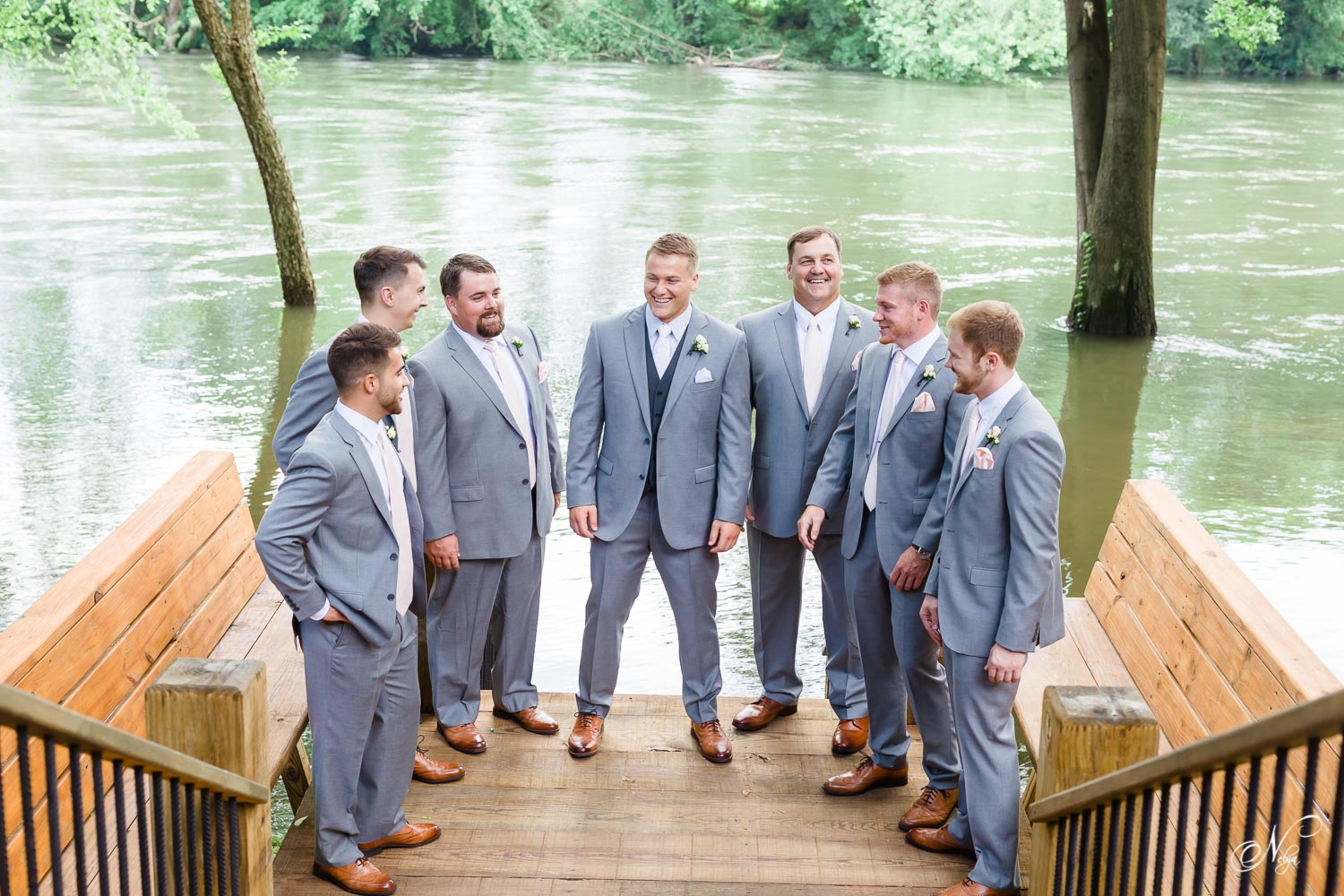 large group of groomsmen in suits chatting by the Hiwassee River with the highest water levels since 1973