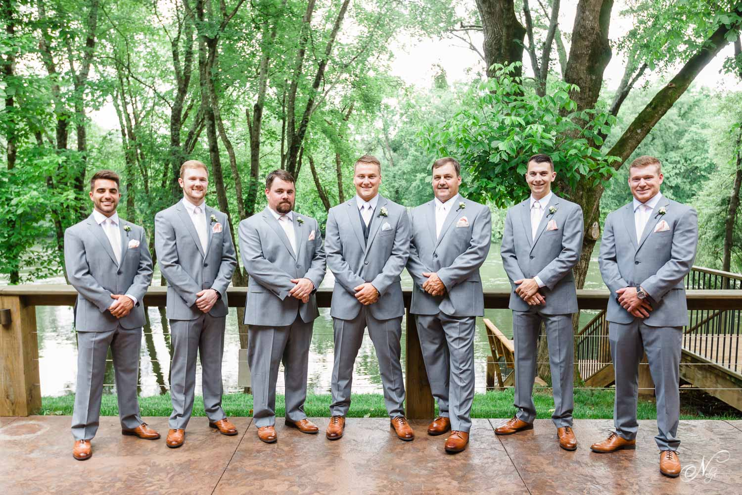 groomsmen in gray jos a banks suits outside of wedding venue near the hiwassee river near Chattanooga TN