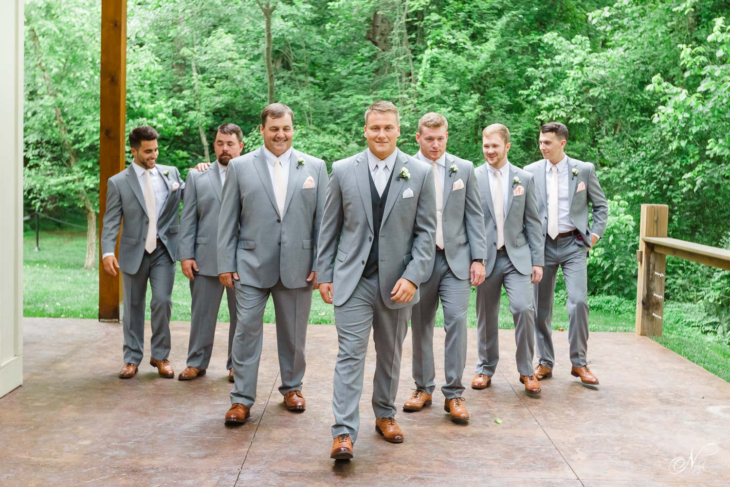 seven groomsmen and groom in gray joseph a Banks suits walking outside in the rain at Hiwassee River Weddings