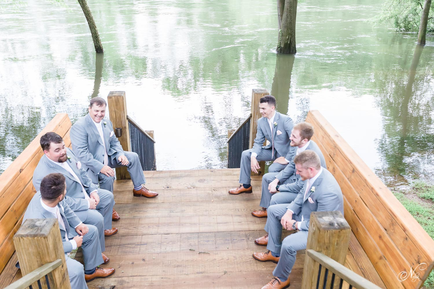 groomsmen sitting outside on wooden bench along the big stair case at Hiwassee River Weddings