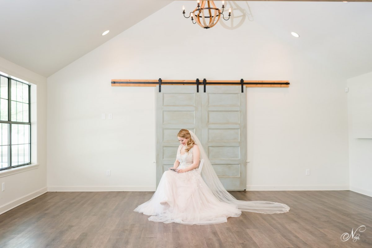 a bride sitting in the middle of a large white room in Chattanooga opening a gift from the groom.