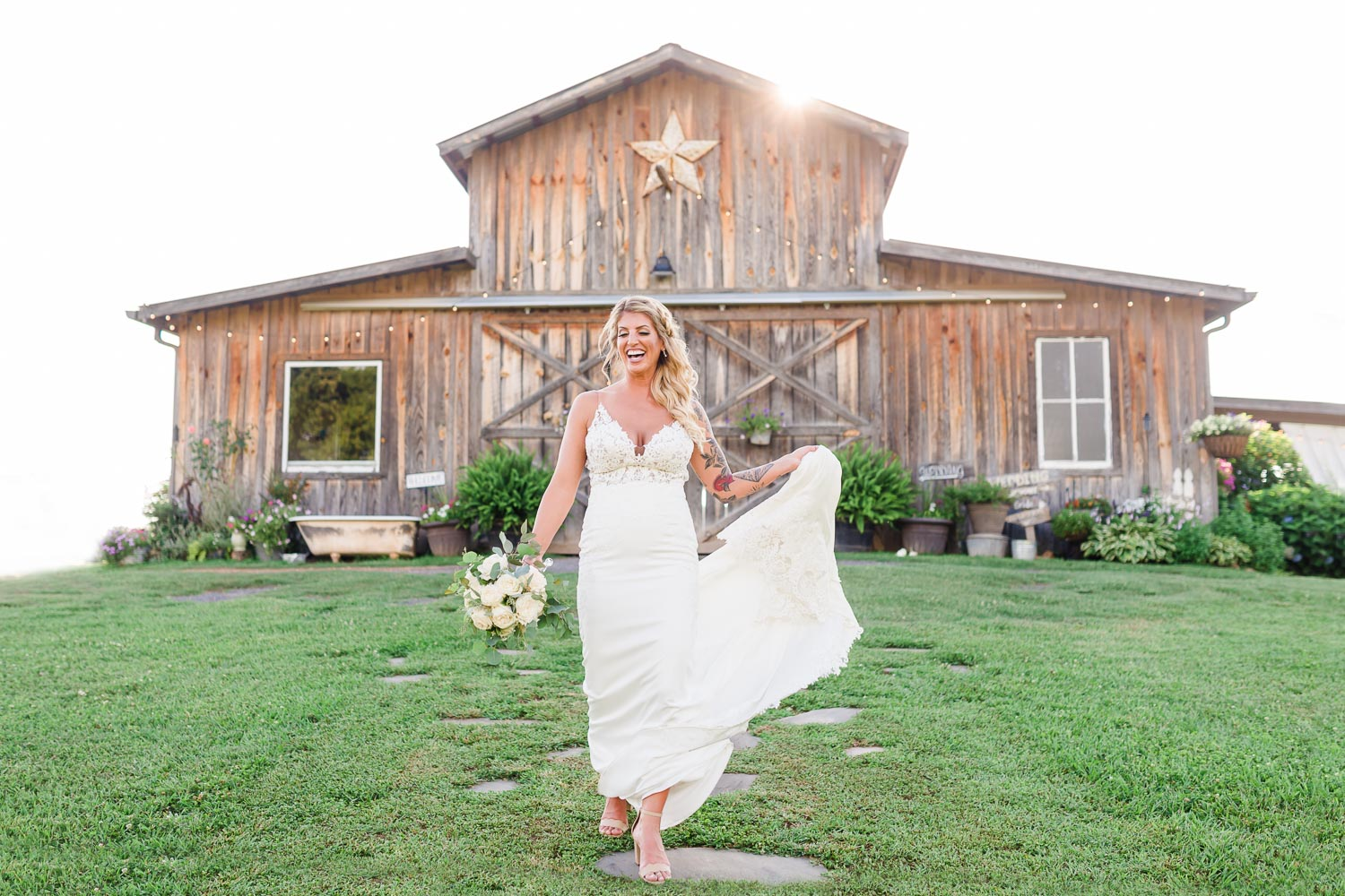 bride walking down stone walkway at the barn at Drewia Hill with barn in the background