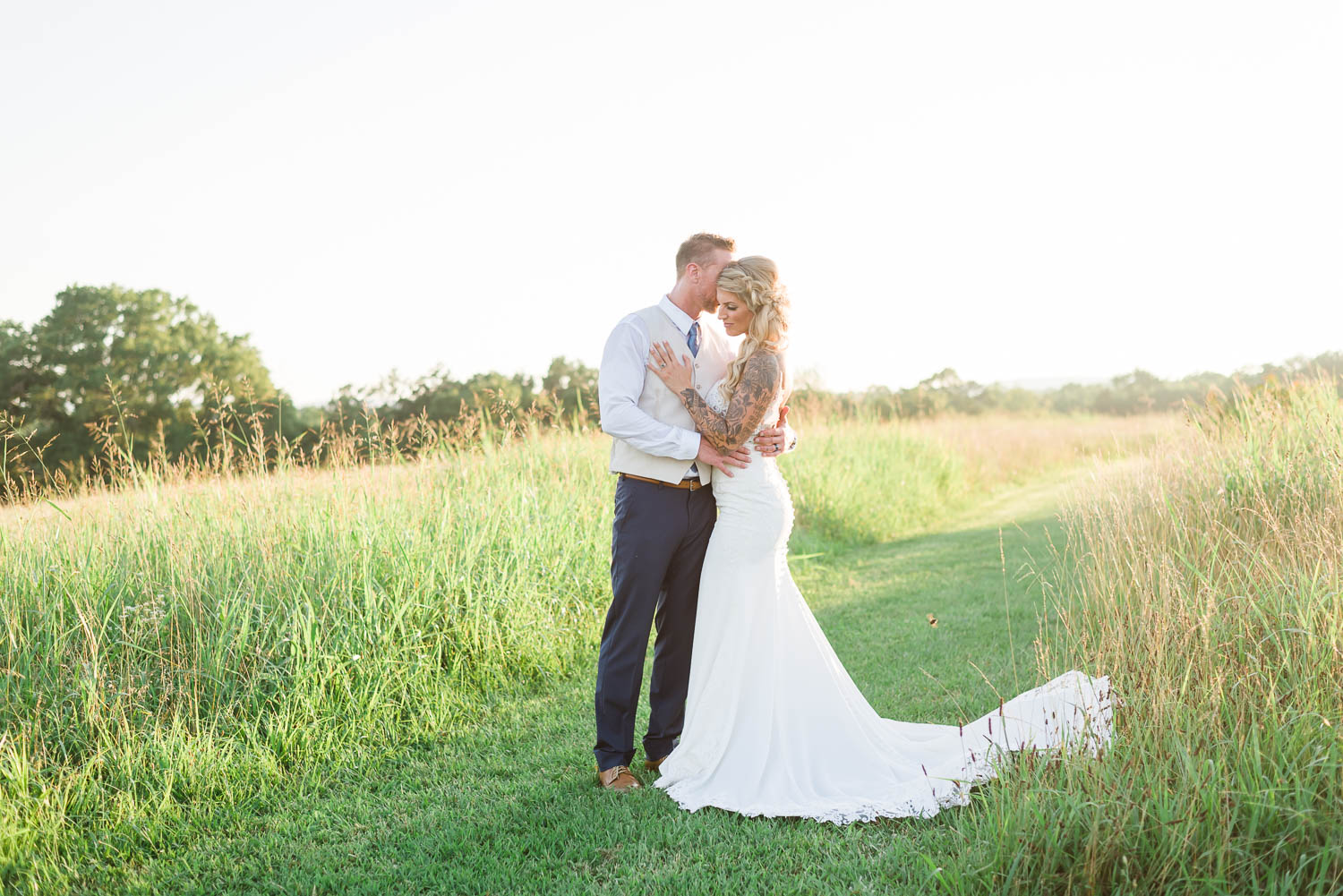 Bride and Groom out on a sundrenched field next to The barn at Drewia Hill wedding venue in Sale Creek TN