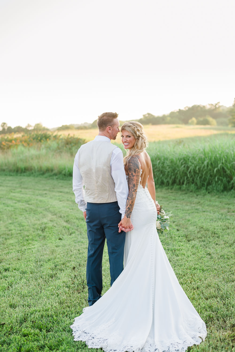 bride in open back lace wedding dress and groom in navy blue pants and cream colored vest outside at The Barn at Drewia Hill in Sale Creek TN
