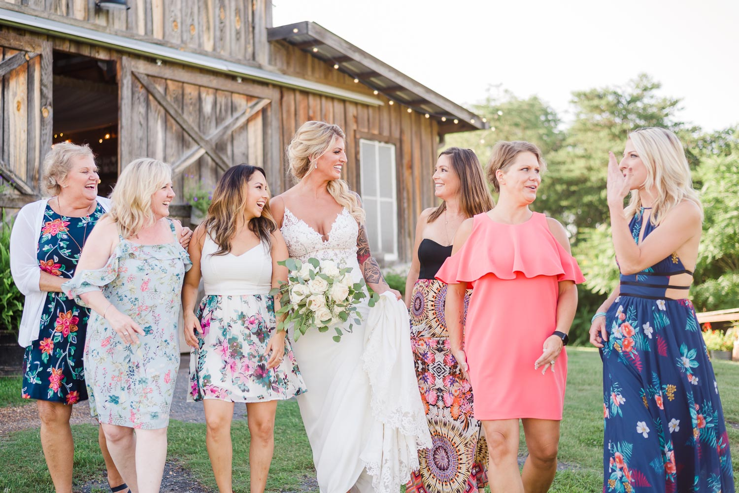 multiple women in floral and pastel colored summer dresses walking with bride on her wedding day at The Barn at Drewia Hill in Sale Creek TN