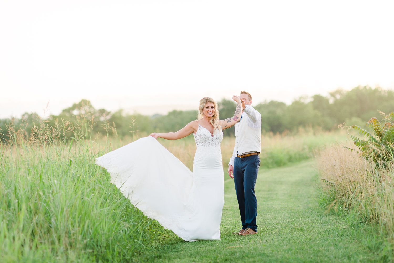 bride being twirled around dancing with groom in tall grass field in front of barn venue in TN