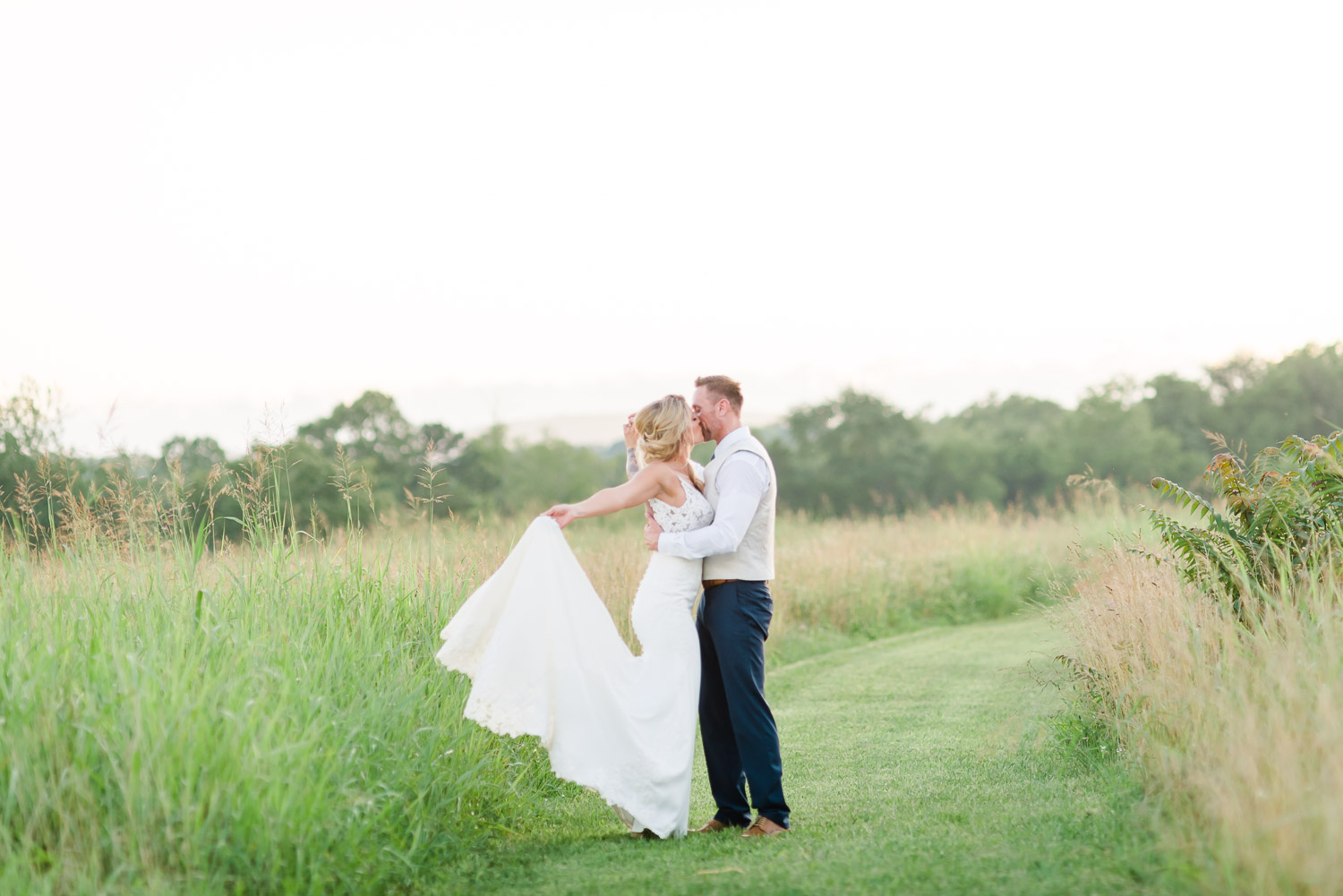 bride embracing groom in white wedding dress in open field at sunset