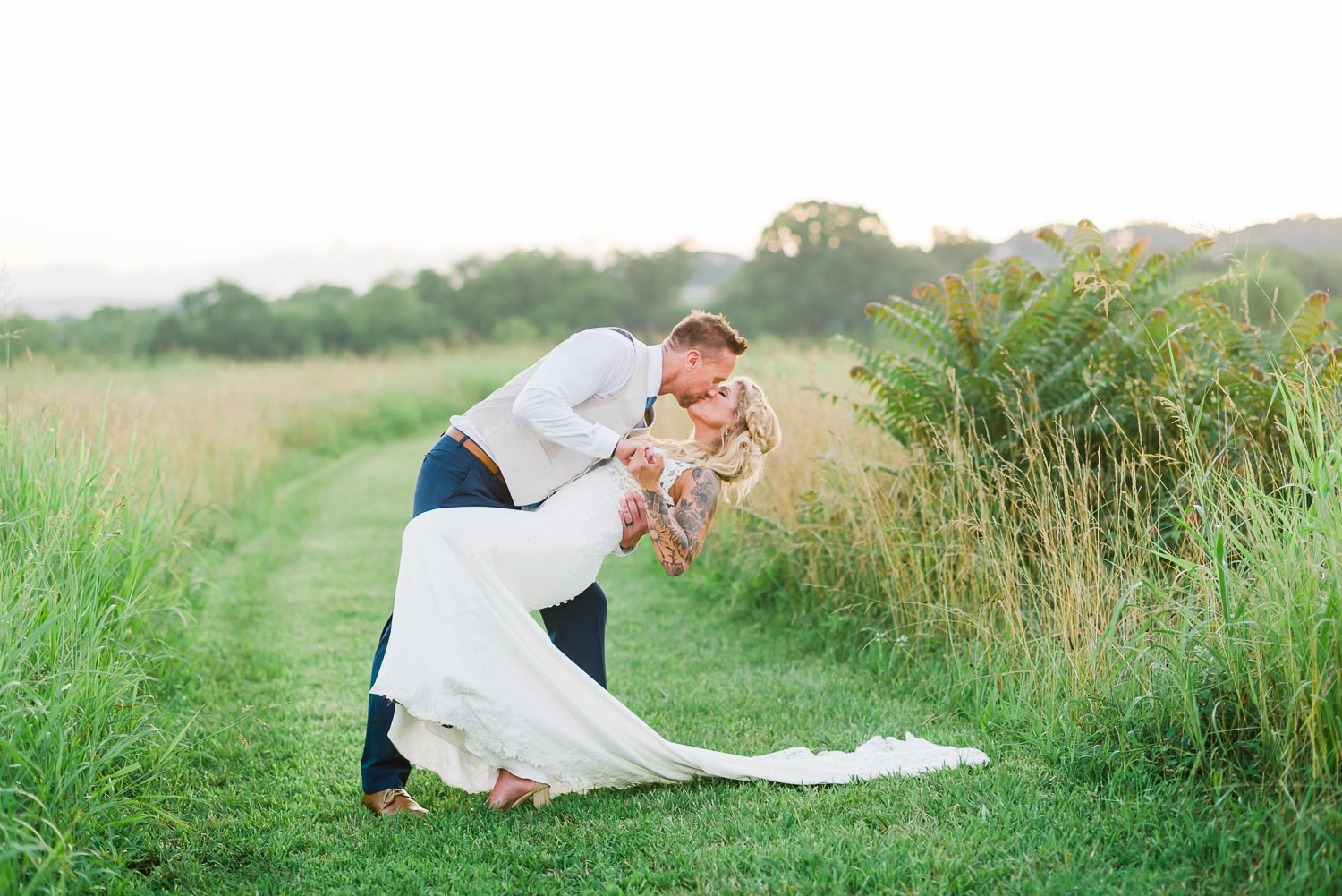 groom dipping his bride back for a kiss outside in a grassy field during wedding photos in Tennessee