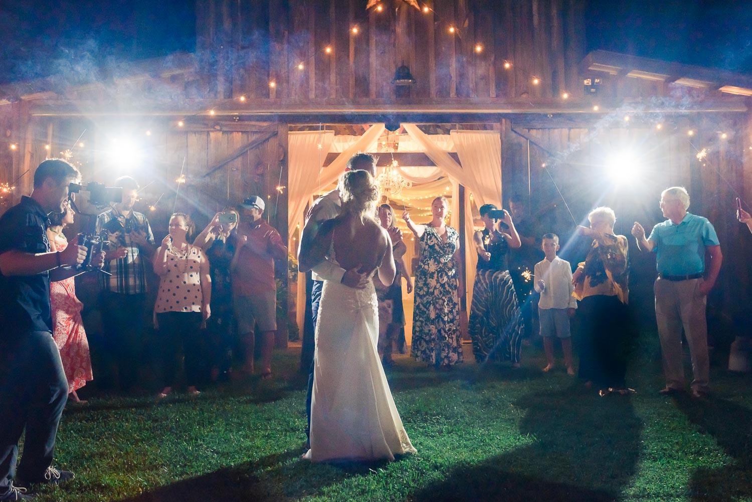 wedding couple dancing their first dance with guests standing in a circle holding sparklers in front of the Barn at Drewia Hill near Chattanooga TN