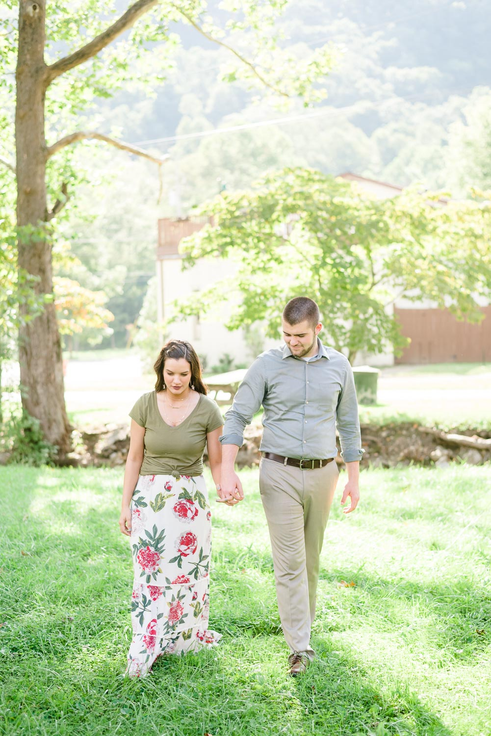 engaged couple walking in glowy sunshine under trees in Cumberland Gap TN