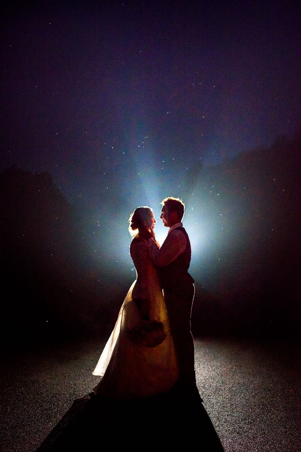 Silhouettes of a bride and groom at night in the fog outside of the 4 Points Farm wedding venue in Sevierville TN