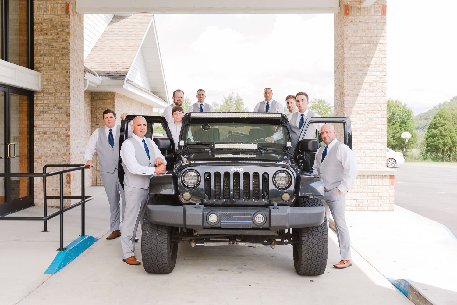 guys outside in gray suits gathered around a black jeep in Sevierville TN