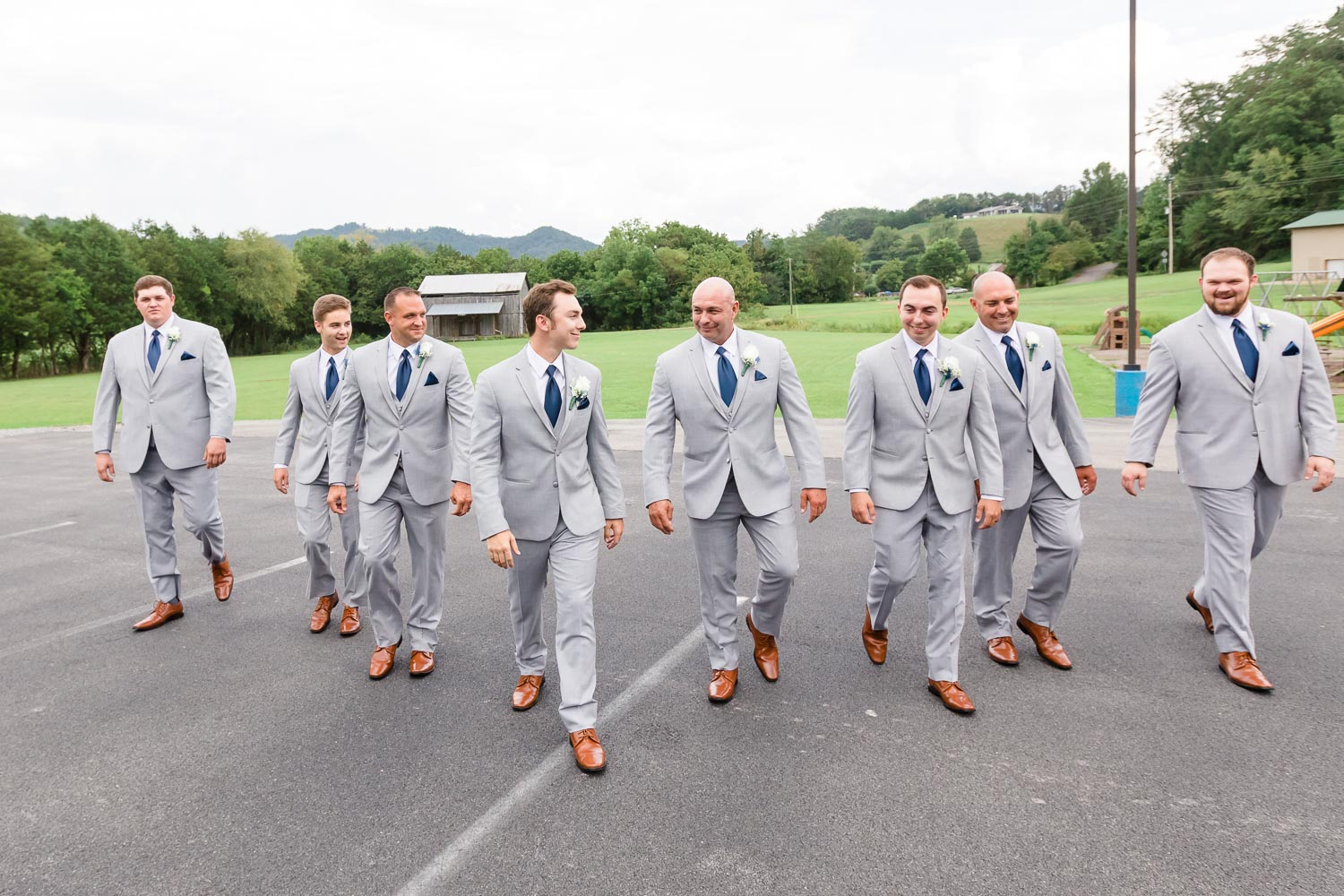 groomsmen wearing gray suits and navy neckties with brown shoes walking outside in Gatlinburg TN