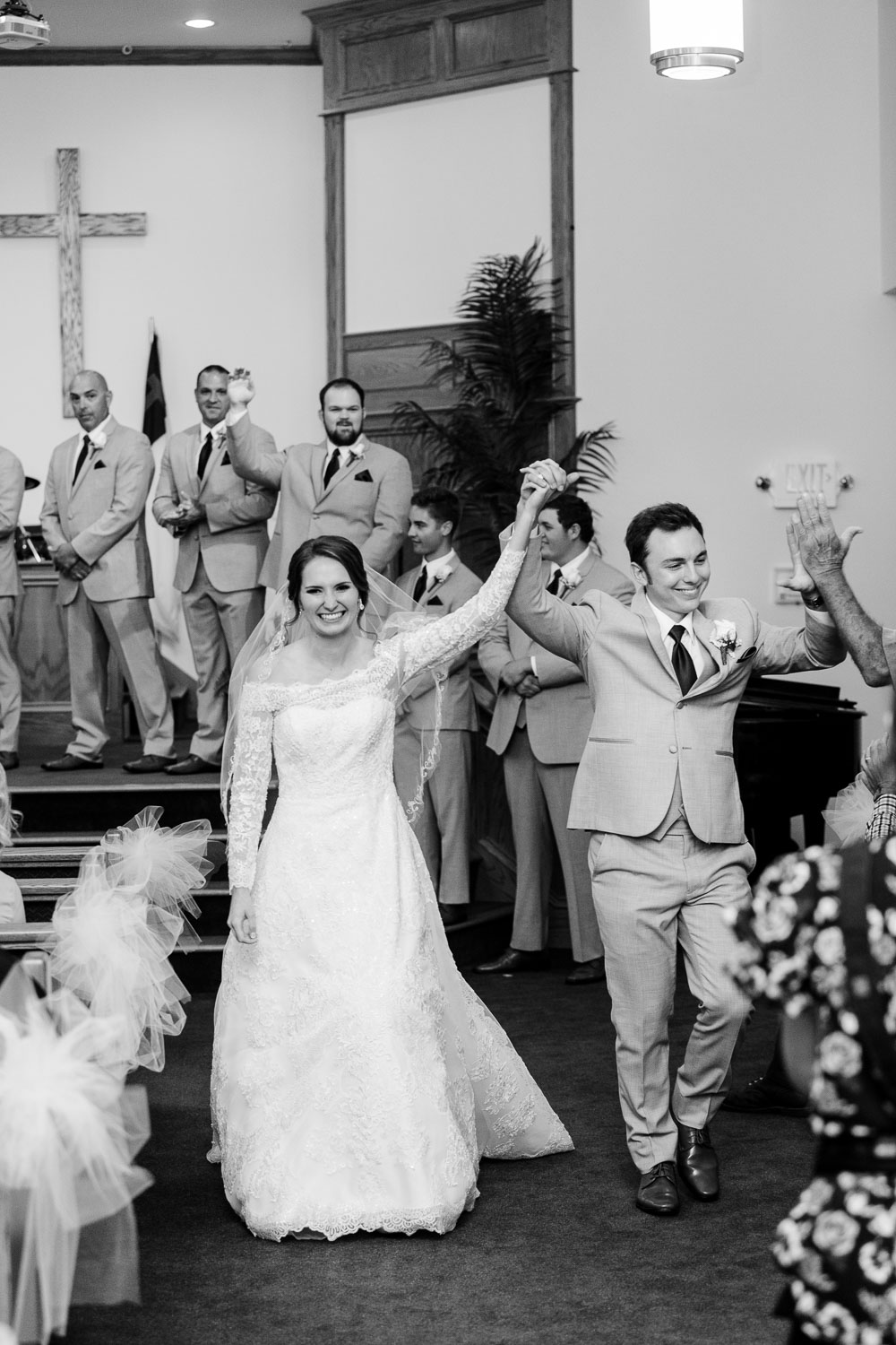 bride and groom running out of the church cheering after getting married in Gatlinburg TN