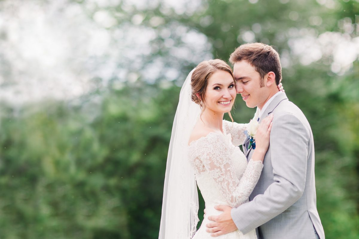bride smiling at the camera in an off the shoulder lace sleeved Oleg Cassini wedding dress and groom in light gray suit just soaking up the moment with his new wife in Gatlinburg TN