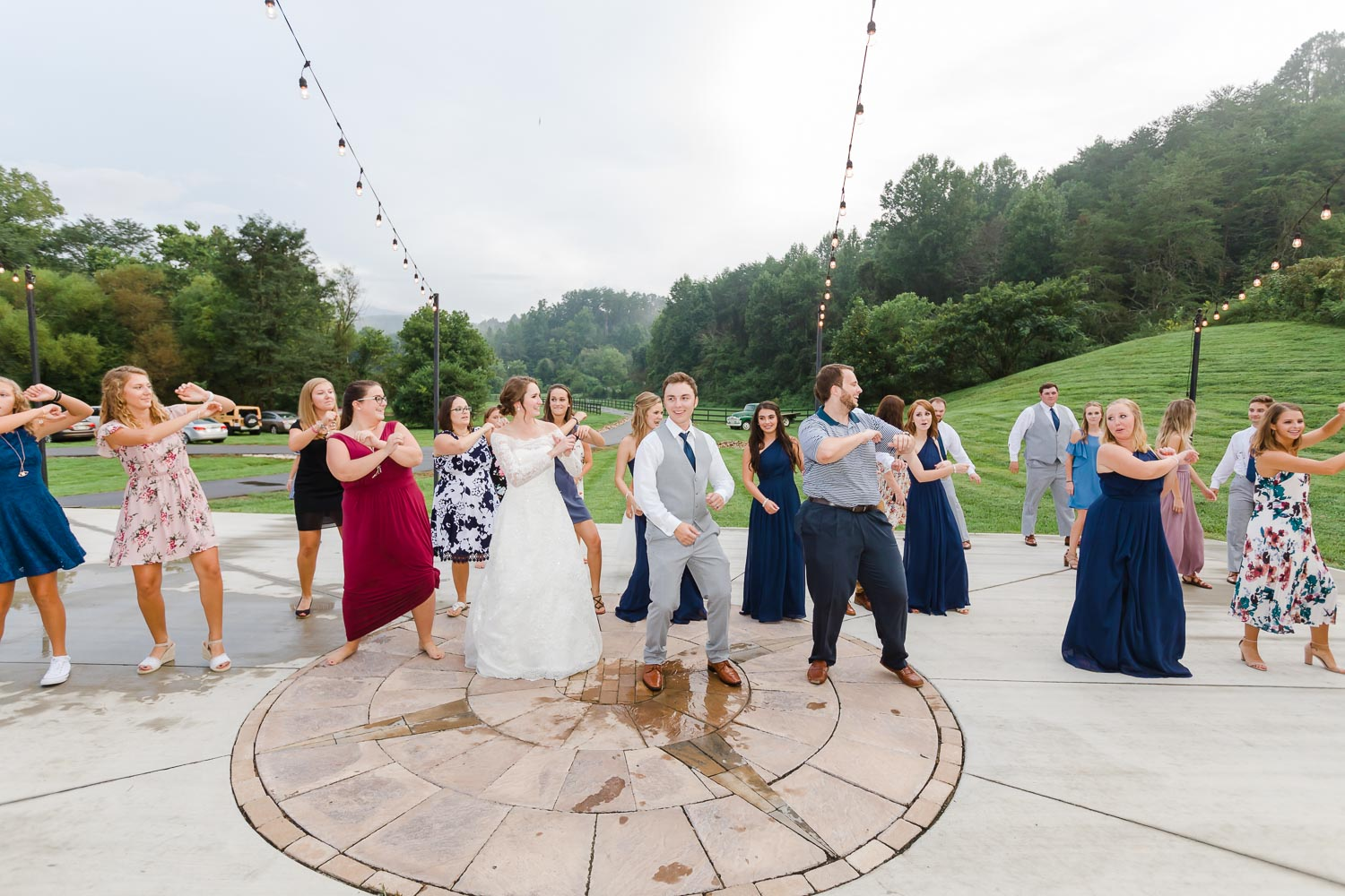 wedding reception dances with guests outdoors under twinkly lights on the patio in front of the Venue at 4 Points Farm in TN