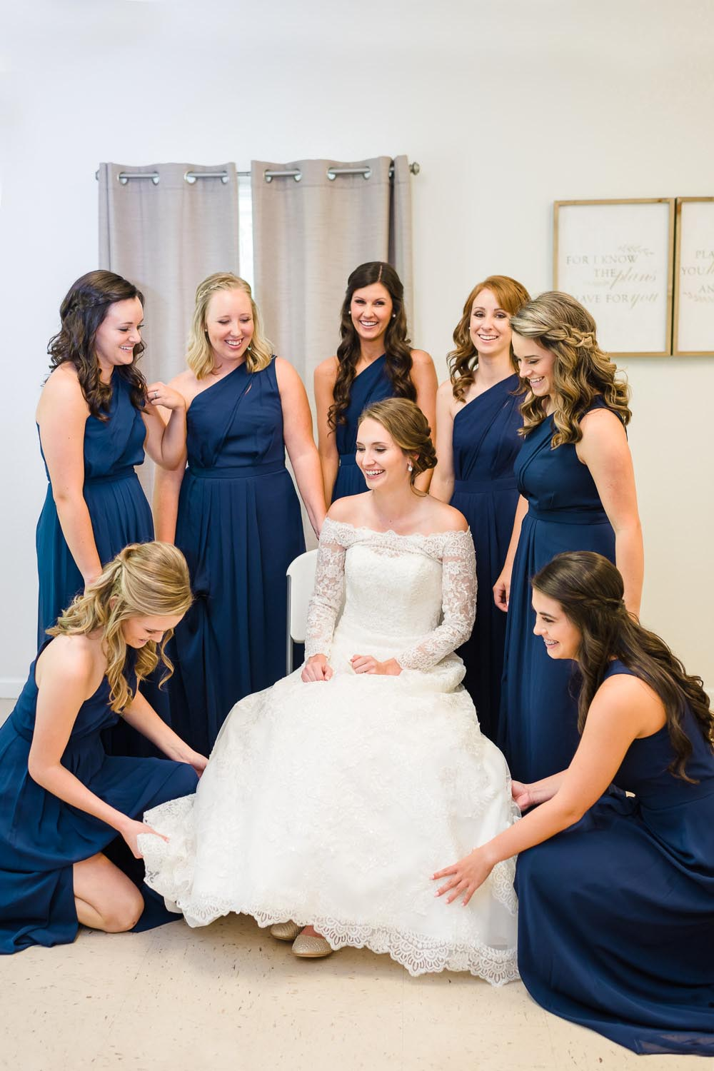 bride sitting with bridesmaids in navy dresses around her getting readdy and adjusting her dress in Gatlinburg TN