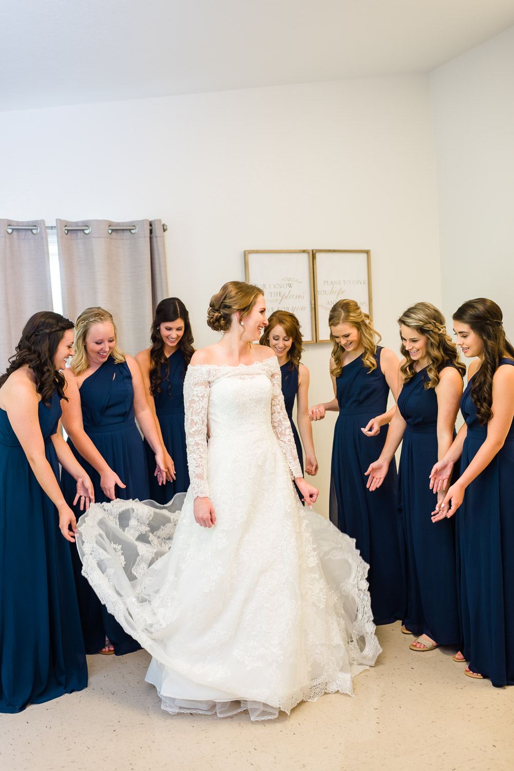 bride and girls in navy one strap long bridesmaids dresses adjusting bride's dress.